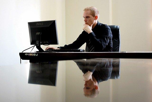 zamyšlený podnikatel koukající do počítače